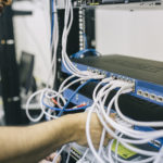 A man switching cables on an internet router.